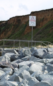 Dry stones, beneath crumbly cliffs with warning sign, Ruth's coastal walk.