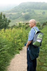 John carrying rucksack, path goes up and down ahead. Ruth's coastal walk.