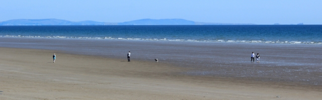 beach at Pendine, Gower in distance, Ruth hiking in Wales