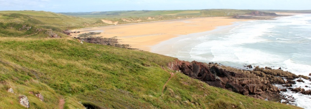looking back Freshwater West, Ruth hiking in Wales