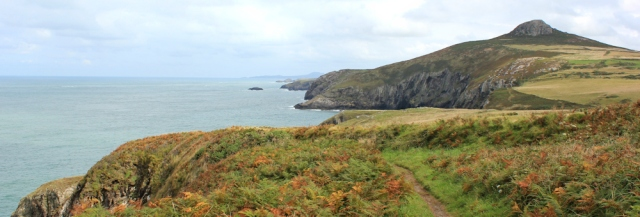 Carn Penberry looms, Ruth walking the Pembrokeshire Coast Path
