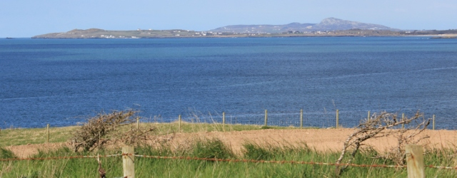 Holy Island in the distance, Ruth hiking in Anglesey,