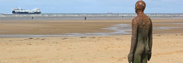 07 heroic Gormleys, watching ships, Ruth hiking on Crosby Beach