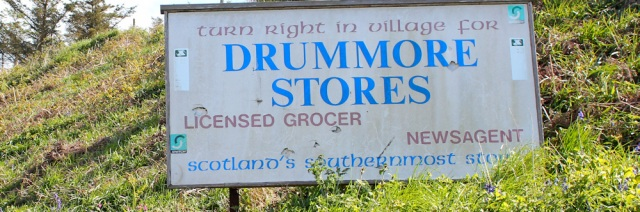 35 Sign for Drummore Stores, Ruth walking the Mull of Galloway Trail