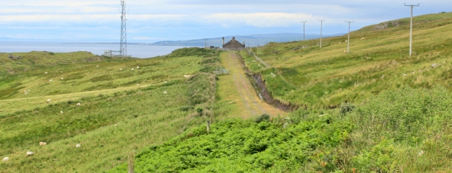 32 mast and ruined farm, Ruth walking the Ayrshire Coastal Path, Scotland
