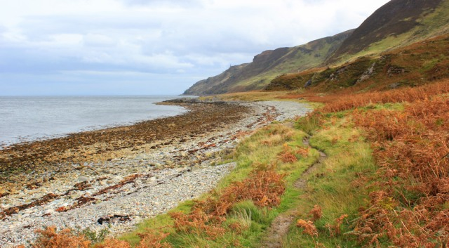 32 Millstone Point ahead, Ruth walking the north shore of Arran