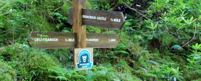 13 signpost in Duncraig woods, Ruth hiking round the coast of Scotland