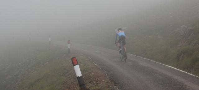 31 cyclist near the top, in the mist, Bealach na Ba, Ruth's coastal walk Scottish Highlands